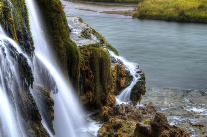 waterfall along the edge of a river.