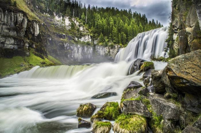 waterfall crashing into a river.
