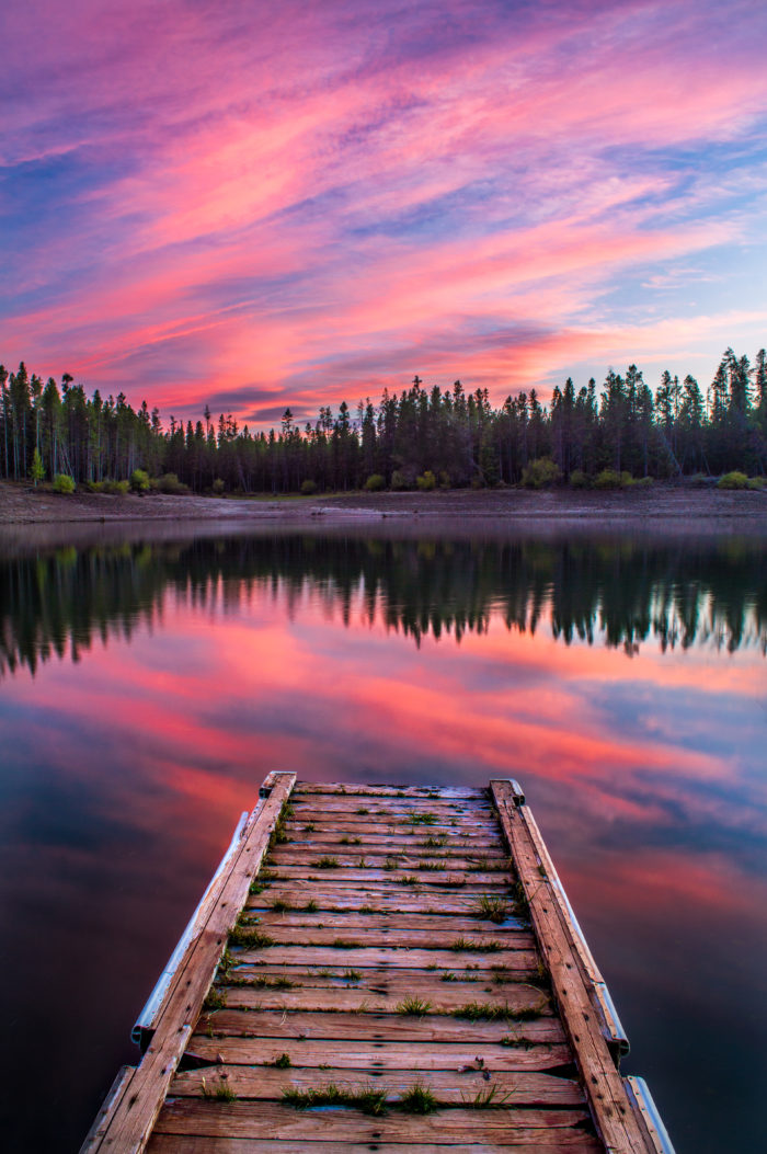 sunset over a dock floating in the water.
