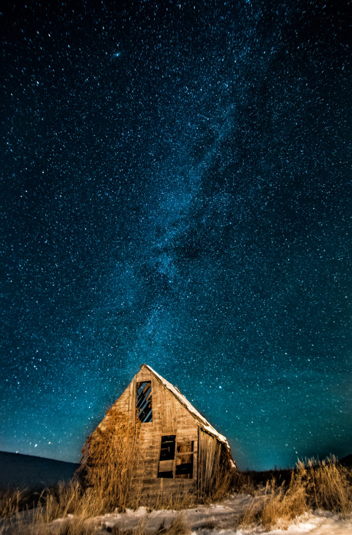 starry night behind an old wooden building.