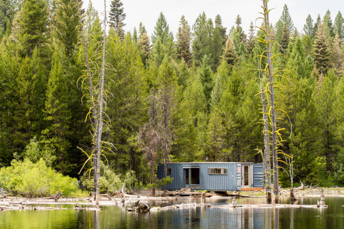 Old shipping container turned into a cabin on the side of a lake.