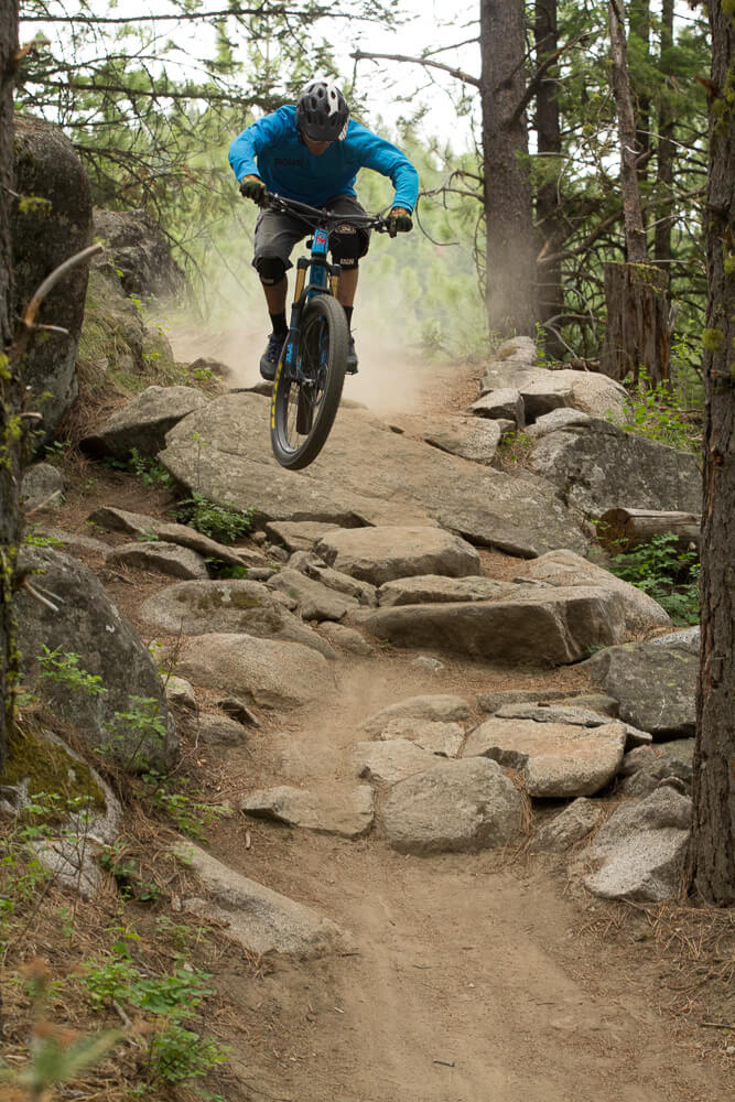mountain bike rider dropping down steep path
