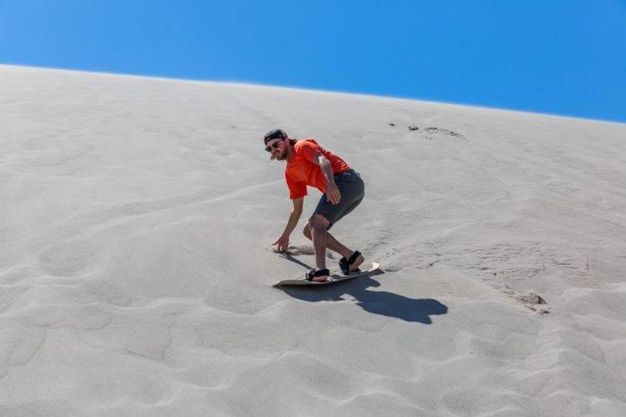 man sandboarding on a sand dune.