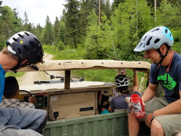 Two cyclists on an old military vehicle.