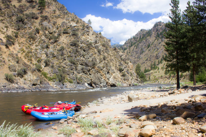 rafts sitting in the Salmon River with mountains in background