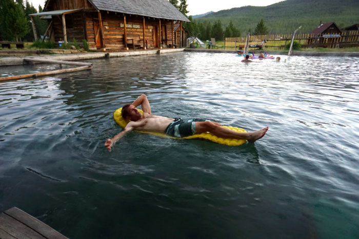 Man floating in hot pool on a raft