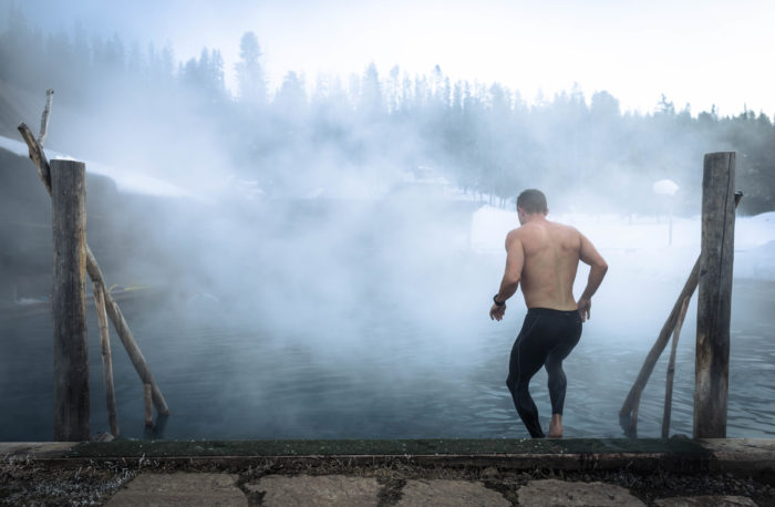man walking down into steaming hot pool