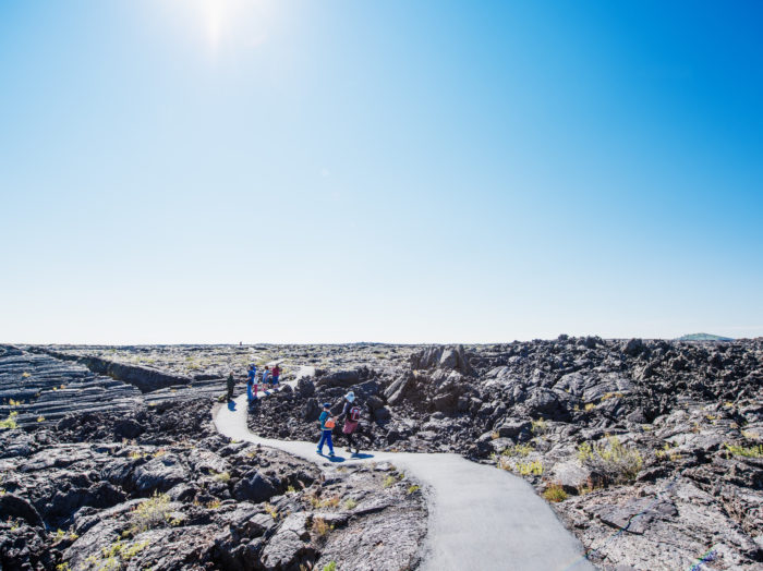 Exploring Craters of the Moon trails. Photo Credit: Idaho Tourism