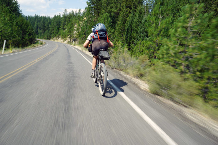 cyclist riding along a paved road in the mountains