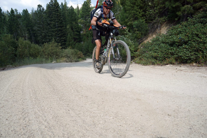cyclist pedaling up a gravel road