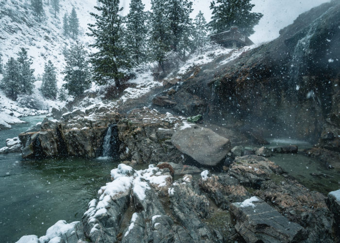 natural hot springs with snow falling