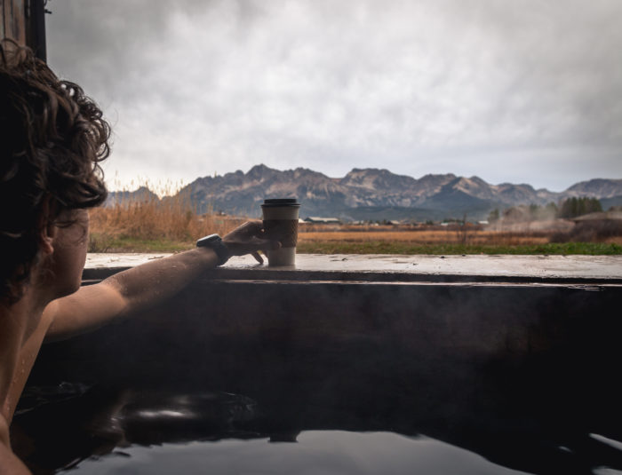 man sipping coffee while soaking in a hot spring