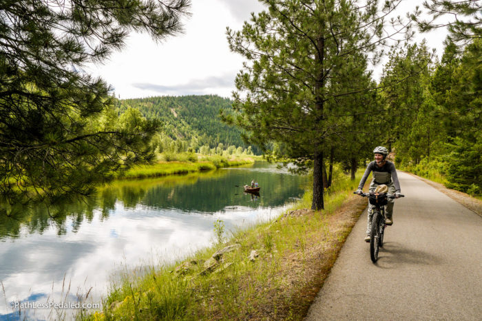 cyclist riding along the river