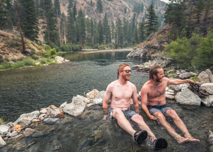 two men sitting in a natural hot pool along the river