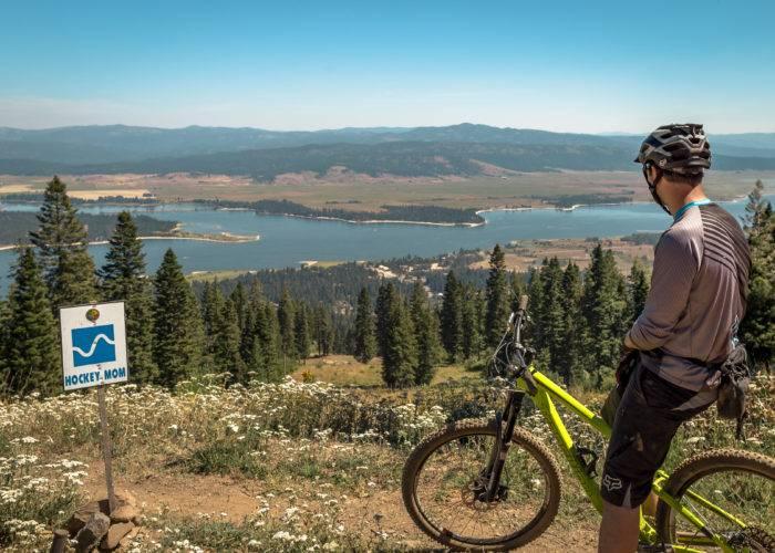 Man on mountain bike looks over lake