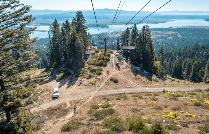 mountain bike riders stand beneath mountain lift.