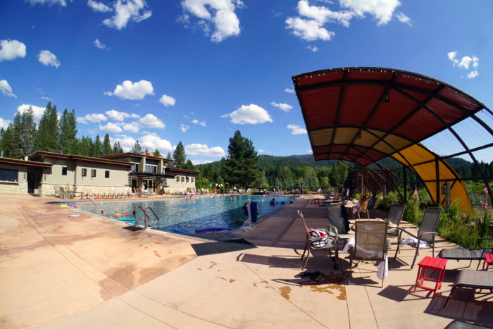 wide shot of hot pool surrounded by pine trees