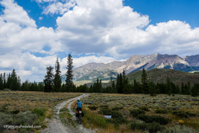 cyclist riding a trail with mountains in the background