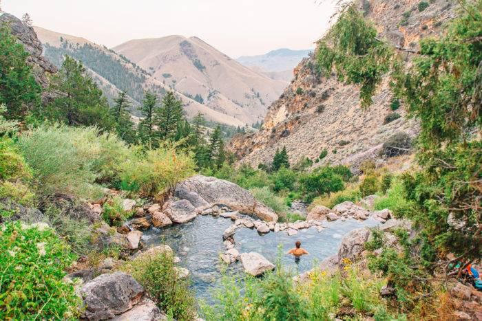 woman sitting in mountain hot pool