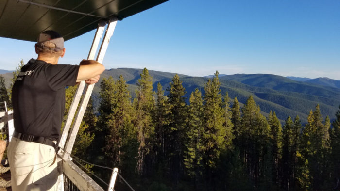 man looking out over forest from fire lookout
