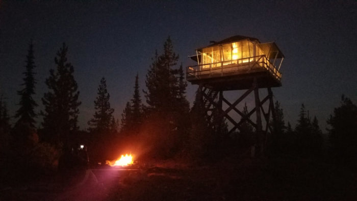 A fire lookout with a campfire burning below