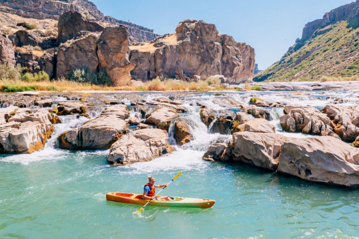 man in kayak near small set of waterfalls