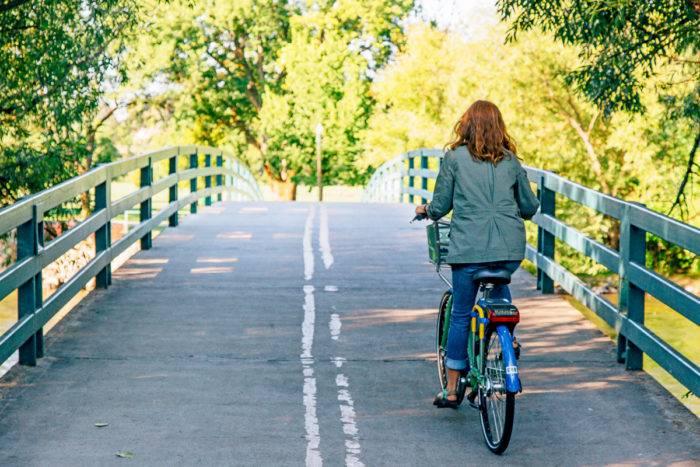 woman riding bike on greenbelt path