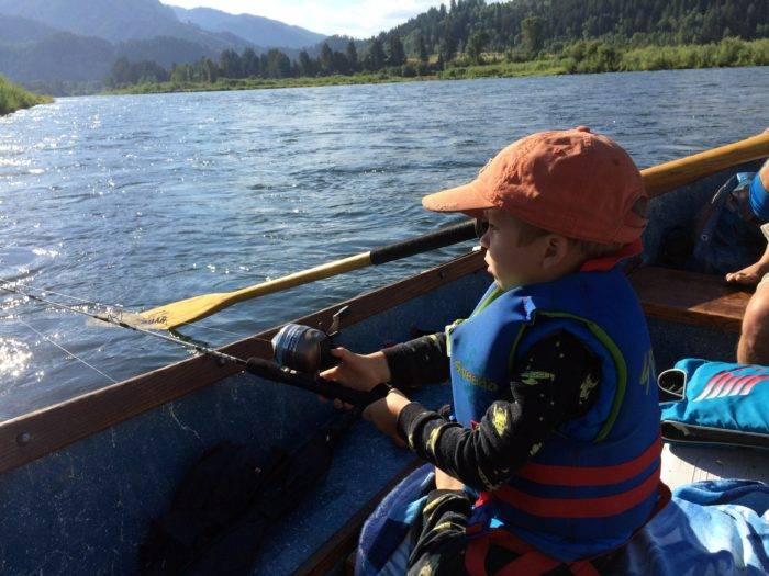 little boy fishing from a drift boat