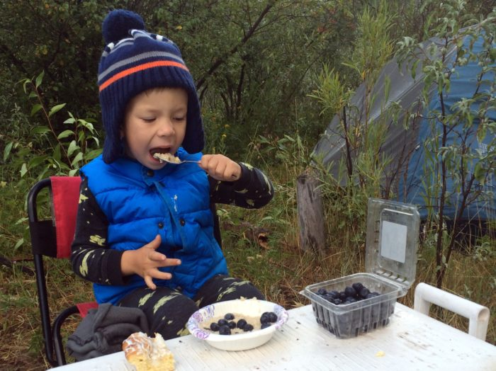 little boy eating oatmeal at a campsite