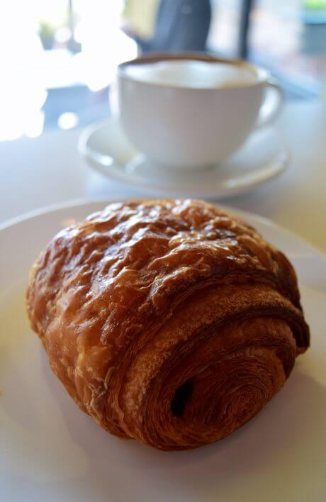 coffee sitting next to a pastry
