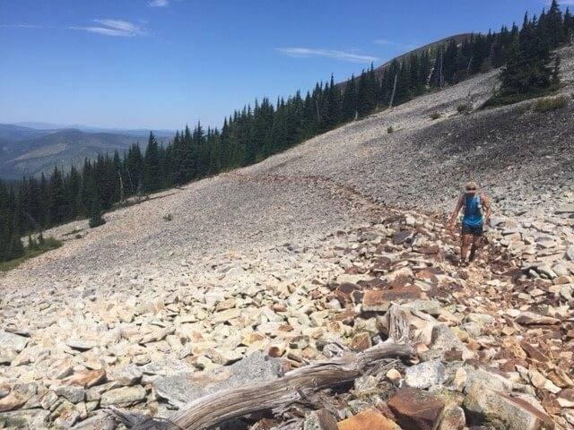 man climbing through large rocky area