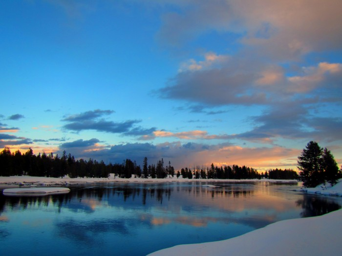 Snow-covered banks surround the calm waters reflecting evening clouds.