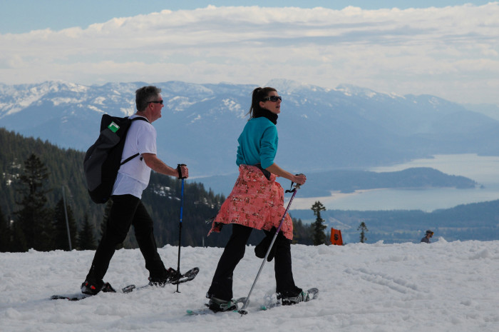 Male and female in short sleeves snowshoeing at Schweitzer Mountain with a view of Lake Pend Oreille below in the distance.