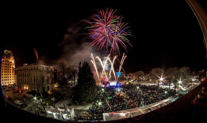 Fireworks exploding while the giant idaho potato is lowered in front of the capital at night.