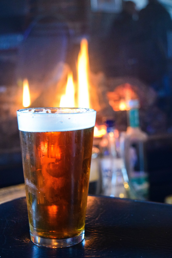 An amber brew silouhetted against a crackling fire at the Capitol Bar in Boise.