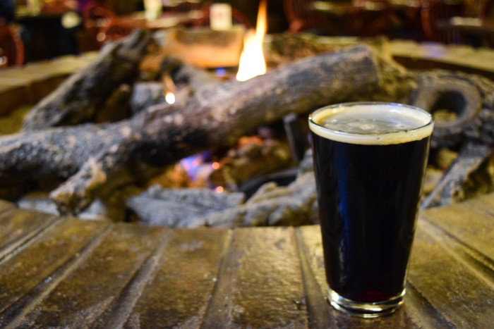 Dark beer sitting on the rim of a fire pit with a crackling fire in the background at Highlands Hollow in Boise.
