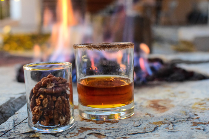 A dark amber cocktail half fills the glass rimmed with a nutty colored salt and sits next to a small glass of spiced pecans with a glowing fire from the fire pit in the background at the Modern Hotel in Boise.