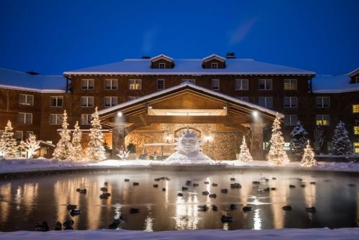 Picture of the Sun Valley Lodge at night with lighted Christmas trees in front.
