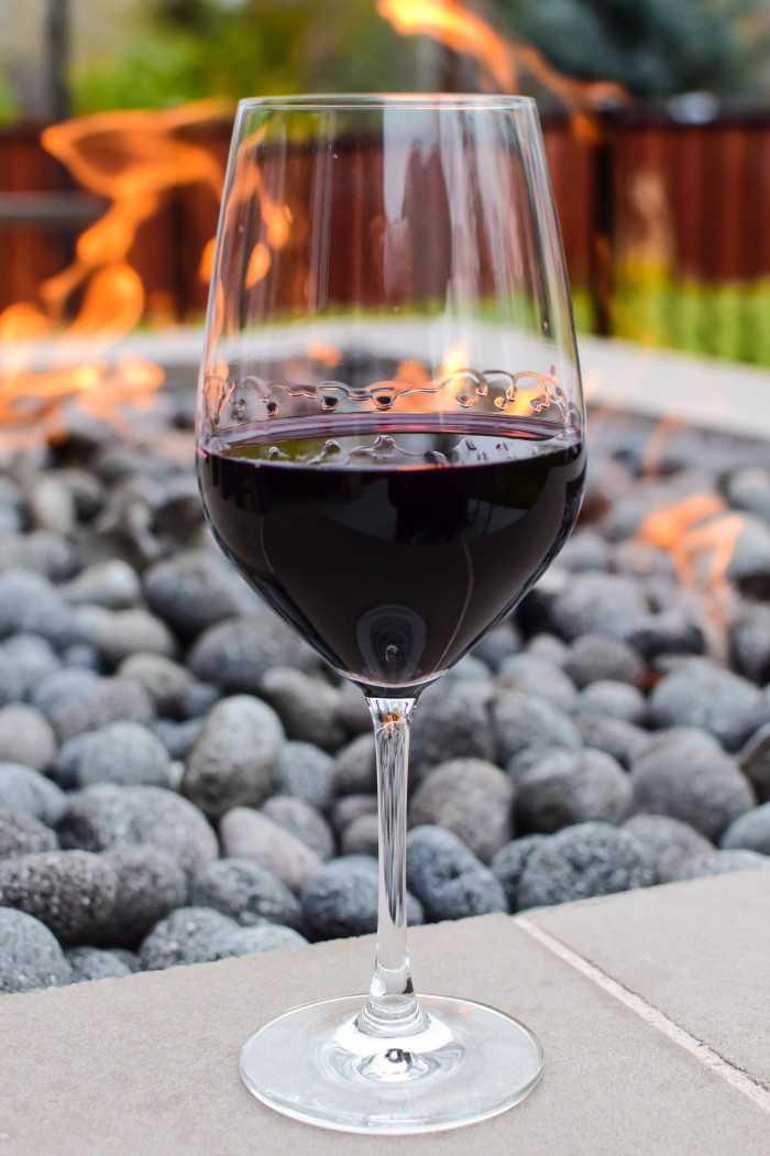 A glass of deep red wine sits in front of a glowing outdoor fire pit at Telaya Wine Co. and Coiled Wines in Boise..