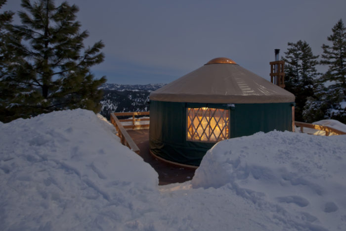 Green-sided yurt with a view of the valley and surrounded by snow.