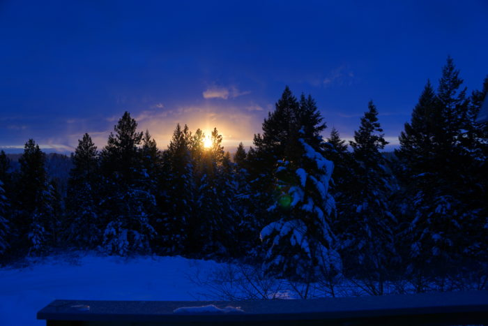 The sky is blue as darkness falls on the snowcovered ground and trees, with just a hint of brightness.