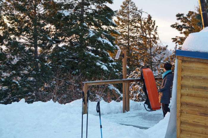 Woman gazes from the deck of the yurt and the surround snow and scenery, with cross country ski poles in the foreground.