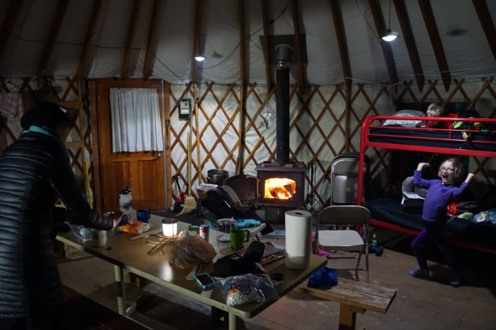 Mom working on dinner with kids and a warming fire in the wood stove in the foreground.
