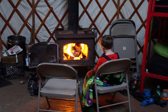 Young boy sits in front of the wood stove.