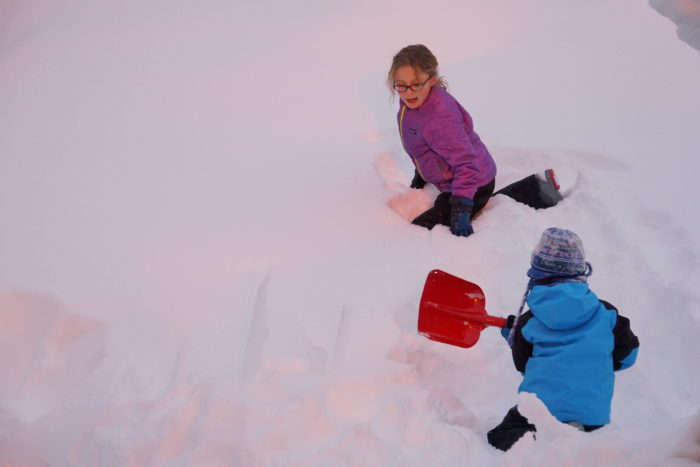 Young girl and boy with snow shovels play in the deep snow.