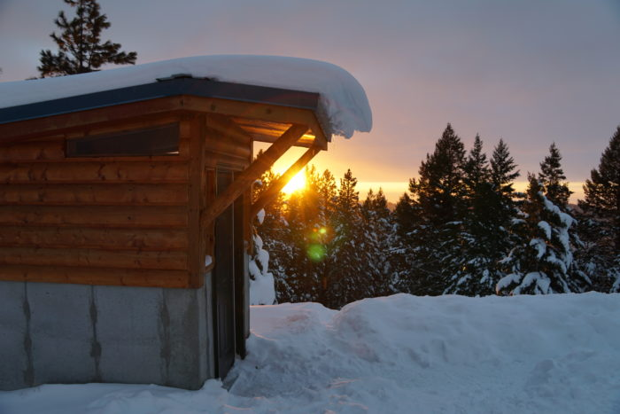 Snow covers the roof and overhang of the yurt's shed while the sun sets in the background.