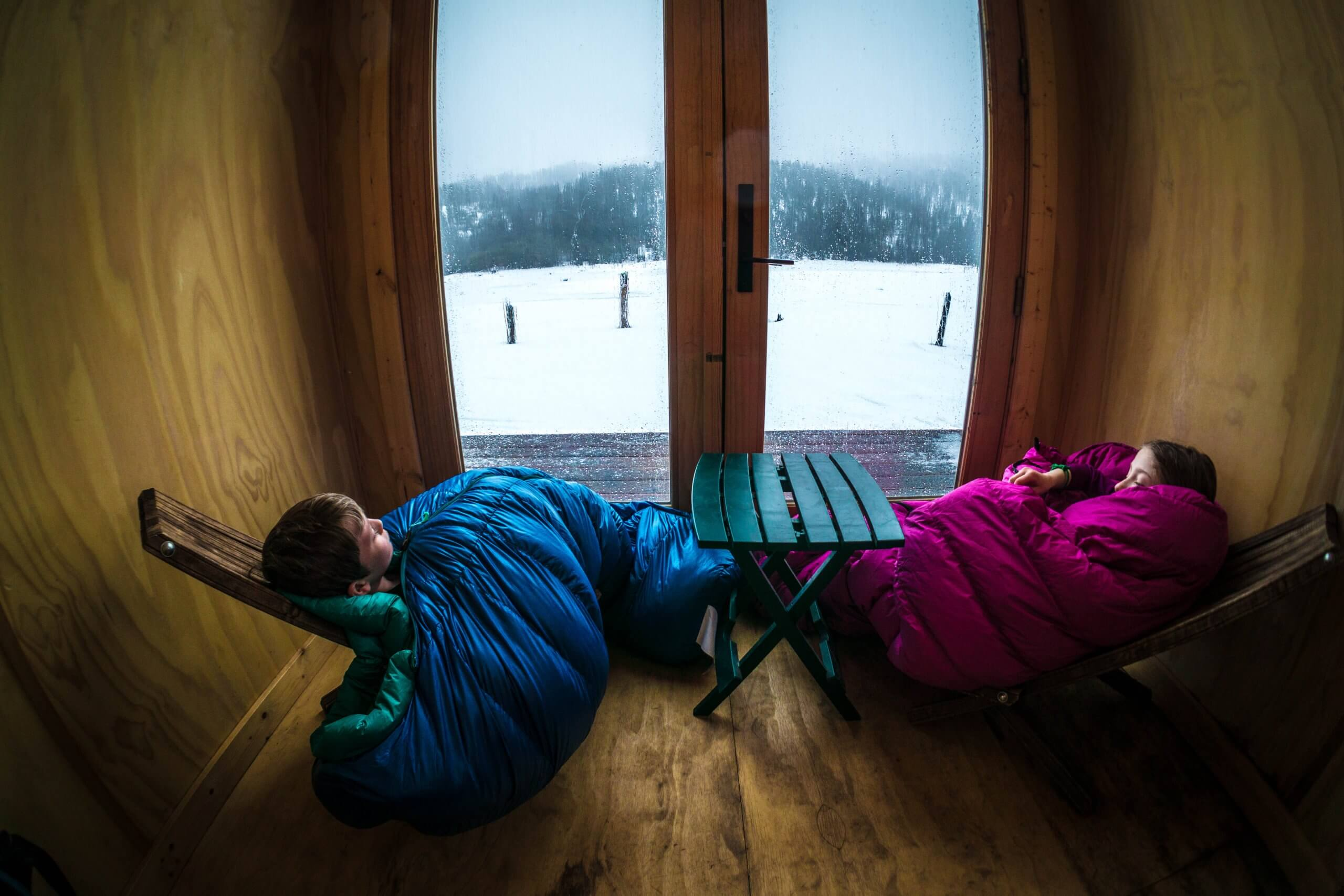 Two kids snuggled up looking out at a lake.