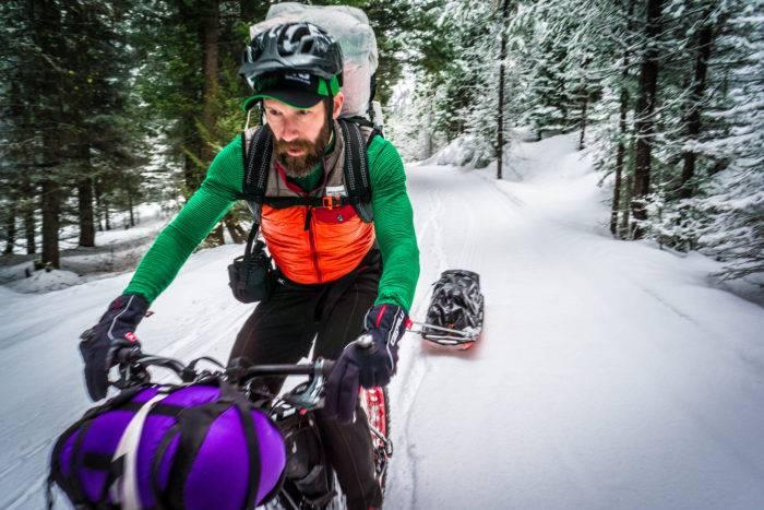 Man riding fat bike on winter trail
