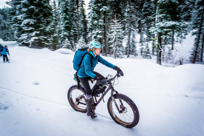 woman riding fat bike on winter trail.