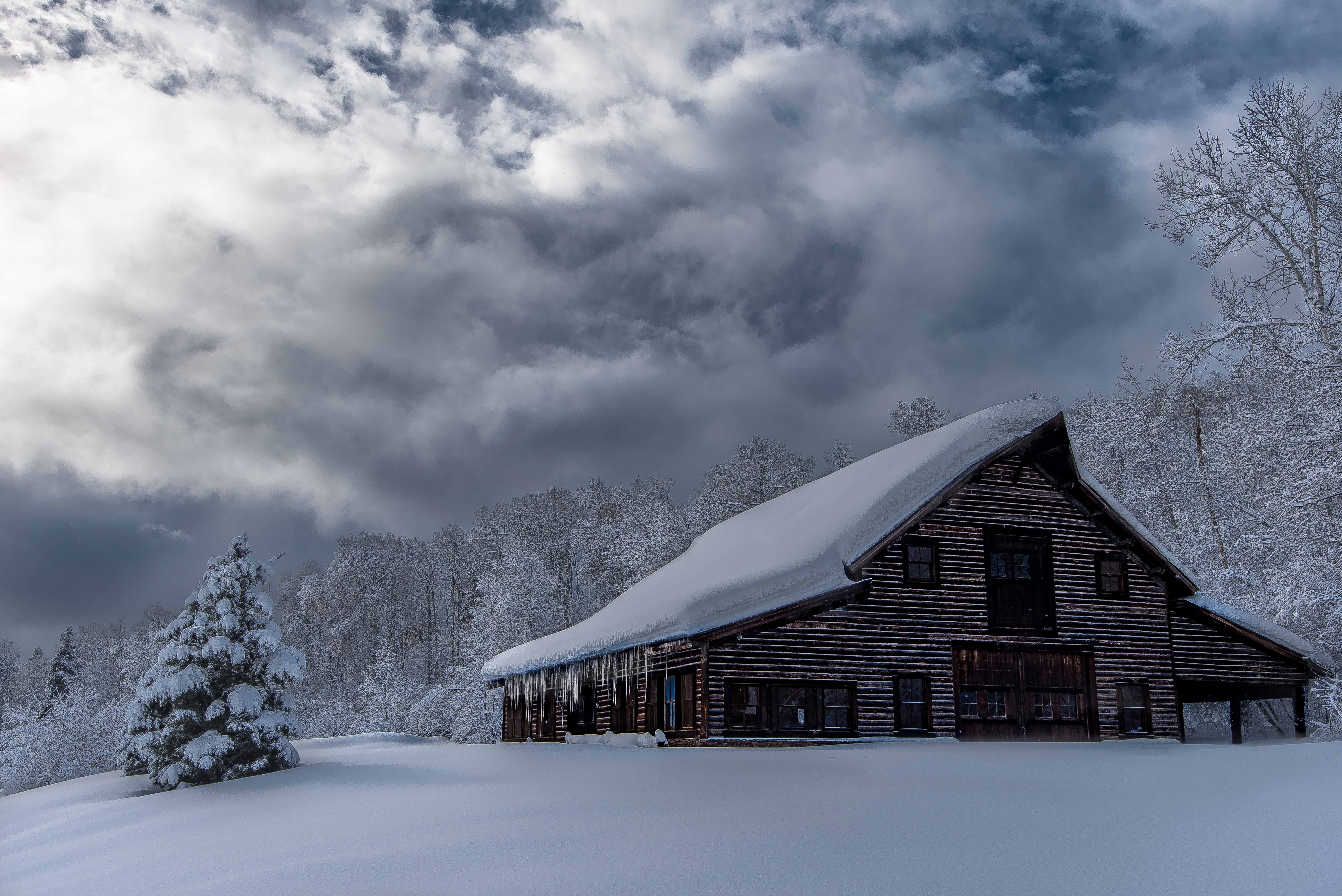 snow covered barn with overcast winter sky